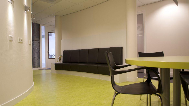 Wachten bij de fysiotherapeut kan op de speciaal ontworpen gebogen bank, of aan de leestafel. De wand achter de bank is zo ontworpen, dat hij het zicht vanuit de gang op de wachtkamer belemmert. Prettig voor de privacy!