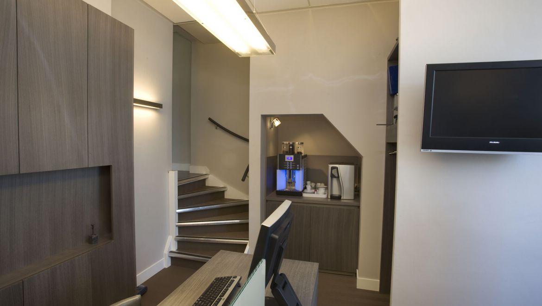 De kleine nis onder één van de trappen onttrekt het koffieapparaat enigszins uit het zicht.