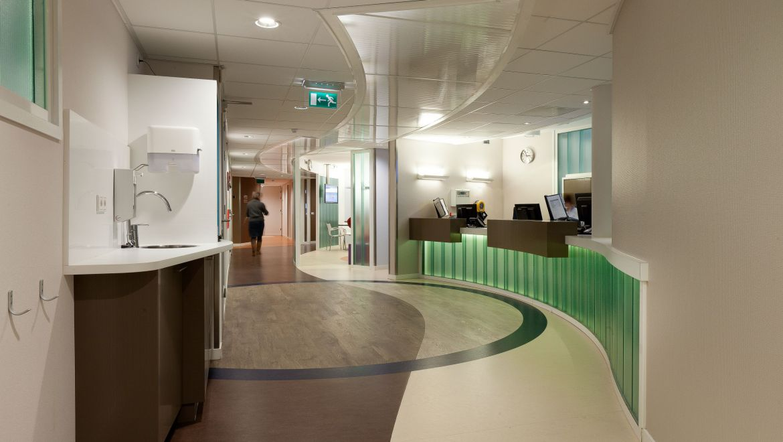 1 Glans en het zachte licht in het plafond reflecteren de verticale lijnen en geven meer ruimtelijkheid aan het interieur. 2 De lange zichtlijnen en de hiërarchie van de gangen creëren een duidelijke looproute voor de bezoeker en scheiden de personeelsgangen.