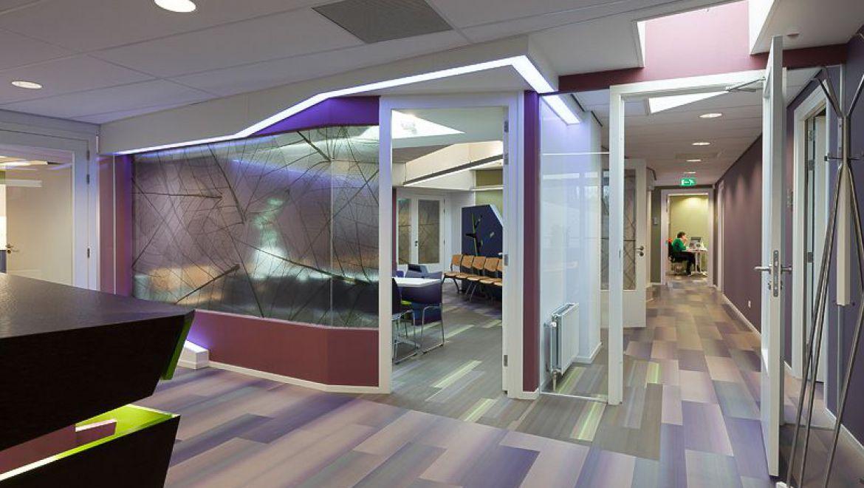 Balie en wachtruimte, vanaf de balie is zicht op de wachtruimte 1 maar door de transparante print op het glas voelt het niet als een vissenkom voor de mensen in de wachtruimte. Verlichting 2 accentueert de centraal gelegen wachtruimte. Doorgang voor medewerkers naar de Back Office 3 en deur naar spreek- en behandelruimtes 4.