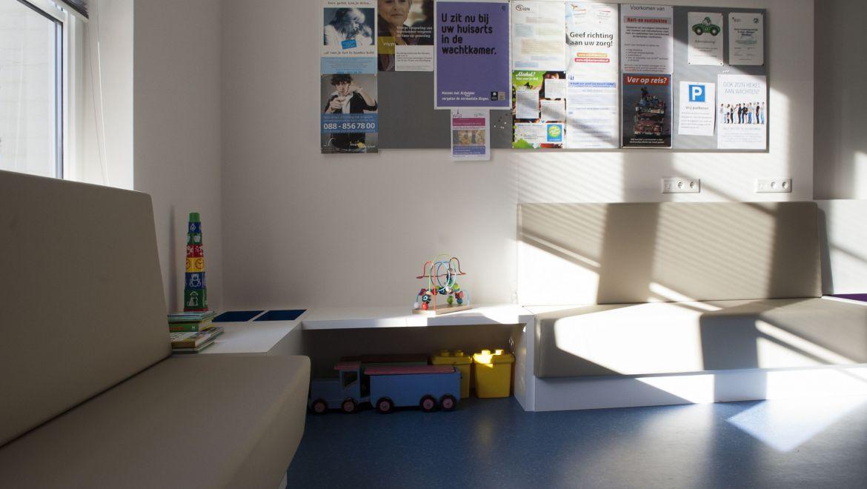 De wachtkamer van de huisartsenpraktijk straalt rust uit. Hier is gekozen voor op maat gemaakte banken met ingebouwde speel- en lectuurbakken